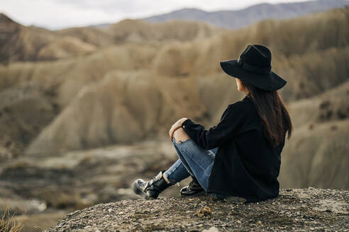 Young woman sitting in desert landscape, Almeria, Andalusia, Spain - MPPF00269