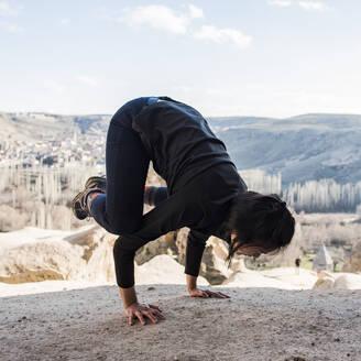 Woman practising yoga in Selime Monastery, Göreme, Cappadocia, Nevsehir, Turkey - CUF53488