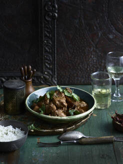 Rustic low key still life with bowl  of chettinad black pepper chicken fry and white wine on table - ISF22860