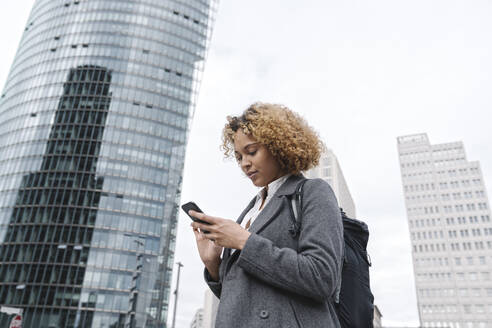 Woman using smartphone with office buildings in background, Berlin, Germany - AHSF01264