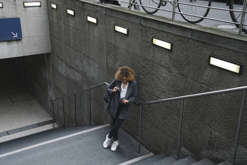 Woman using smartphone at the entrance of a subway station, Berlin, Germany - AHSF01288