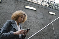 Woman using smartphone at the entrance of a subway station, Berlin, Germany - AHSF01291