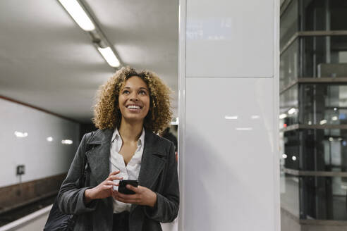 Happy woman with cell phone waiting in subway station - AHSF01294
