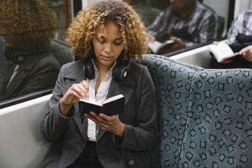 Woman with notebook on a subway - AHSF01300