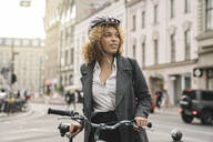 Woman with bicycle in the city, Berlin, Germany - AHSF01312