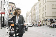 Woman with bicycle in the city, Berlin, Germany - AHSF01315