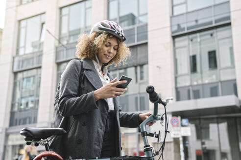 Woman with bicycle and smartphone in the city, Berlin, Germany - AHSF01318