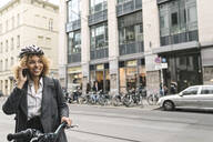 Smiling woman with bicycle talking on the phone in the city, Berlin, Germany - AHSF01321