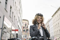 Woman putting on bicycle helmet in the city, Berlin, Germany - AHSF01324
