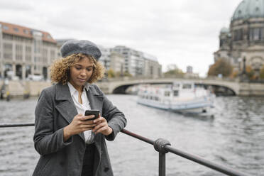 Tourist woman using smartphone in the city with Berlin Cathedral in background, Berlin, Germany - AHSF01327