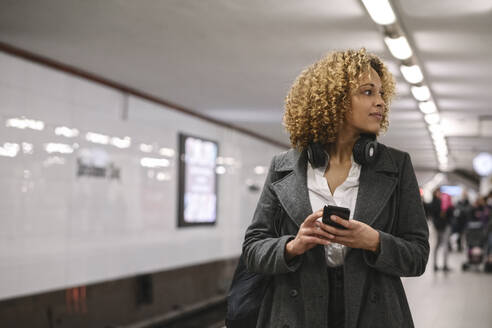 Woman with cell phone waiting in subway station - AHSF01342