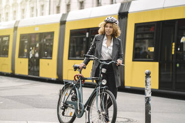 Woman with bicycle commuting in the city, Berlin, Germany - AHSF01345