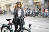 Smiling woman with bicycle talking on the phone in the city, Berlin, Germany - AHSF01348