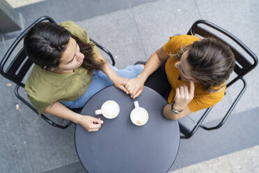 Top view of lesbian couple holding hands at a sidewalk cafe - FBAF00965