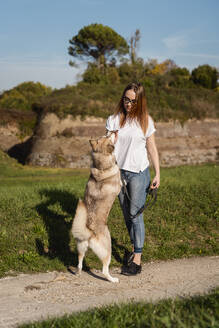 Young woman teaching her dog in nature - MAUF03074