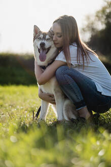 Young woman hugging her dog on a meadow - MAUF03083
