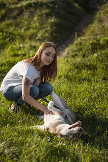 Portrait of young woman stroking her dog on a meadow - MAUF03089