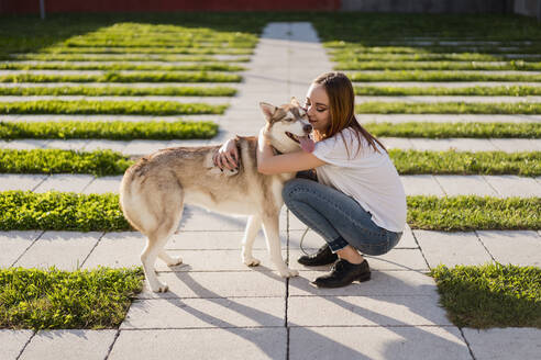 Happy young woman cuddling her dog outdoors - MAUF03095
