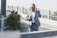 Confident mature businessman with earphones and smartphone on parking deck - UUF19694