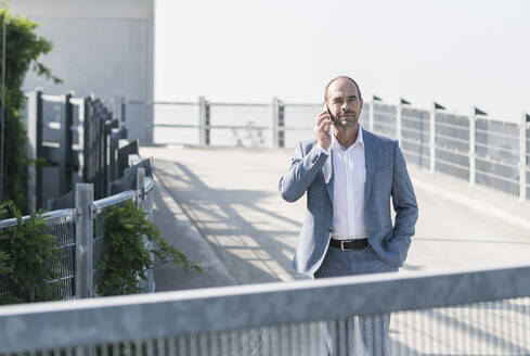 Confident mature businessman on the phone on parking deck - UUF19697