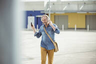 Happy casual mature man with headphones and smartphone walking on parking deck - UUF19712