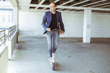 Mature businessman riding e-scooter in parking garage - UUF19715