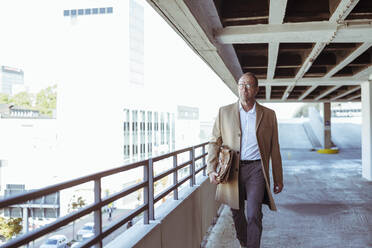 Mature businessman with briefcase walking on parking deck - UUF19718