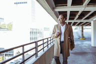 Happy mature businessman with smartphone and briefcase walking on parking deck - UUF19721