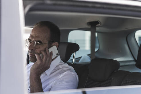 Portrait of mature businessman on the phone in car - UUF19724