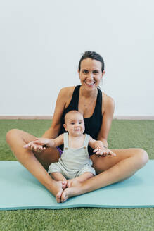 Young mother and baby exercising on yoga mat - MPPF00278