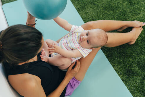 Young mother and baby exercising on yoga mat, playing with a ball - MPPF00287
