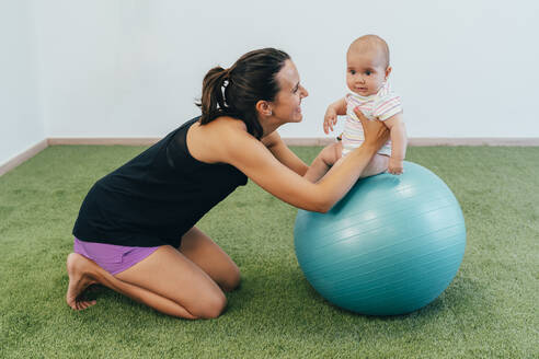 Young mother and baby exercising on fitness ball - MPPF00290
