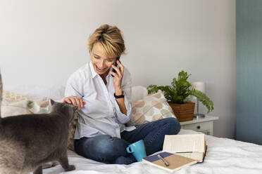 Mature woman with cat sitting on bed at home talking on the phone - VABF02342