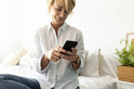 Mature woman sitting on bed at home using smartphone - VABF02357