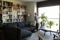 Mature woman standing at the window in living room at home - VABF02399