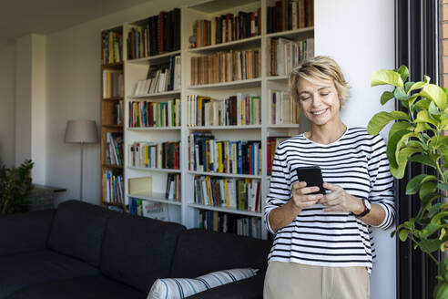 Smiling mature woman standing at the window in living room at home using smartphone - VABF02402
