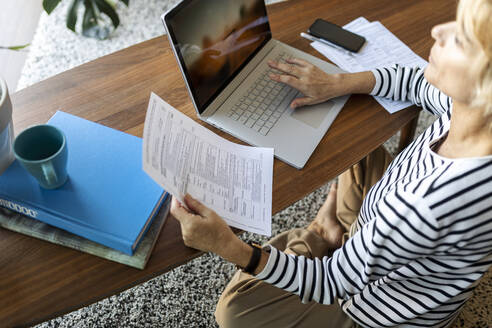 Mature woman with documents using laptop at home - VABF02414