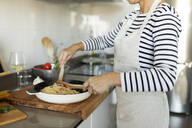 Close-up of woman cooking pasta dish in kitchen at home - VABF02444