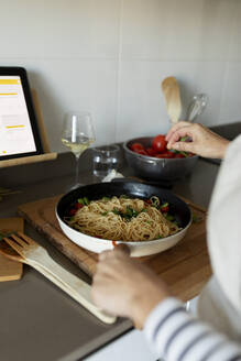 Close-up of woman with tablet cooking pasta dish in kitchen at home - VABF02447