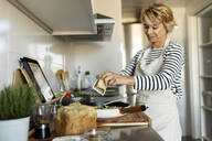 Mature woman with tablet cooking pasta dish in kitchen at home - VABF02450