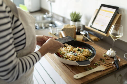 Close-up of woman taking smartphone picture of her pasta dish in kitchen at home - VABF02453