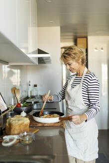 Mature woman cooking pasta dish in kitchen at home - VABF02456