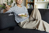 Mature woman eating homemade pasta dish and drinking wine on couch at home - VABF02459