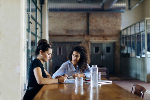 Two young businesswomen talking at conference table in loft office - SODF00354