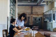 Two young businesswomen talking at conference table in loft office - SODF00357