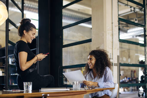 Two happy young businesswomen with smartphone in loft office - SODF00360