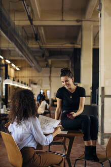 Two happy young businesswomen with smartphone in loft office - SODF00363