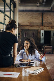 Two young businesswomen with smartphone in loft office - SODF00366