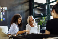 Happy businesswomen with laptop working together in loft office - SODF00369