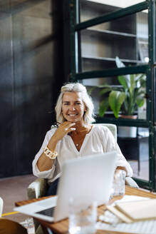Portrait of smiling mature businesswoman with laptop in loft office - SODF00372